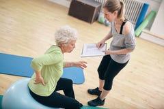 Fysiotherapeut met oude vrouw bij rehab Stock Afbeeldingen