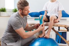 Fysisk terapeut som applicerar det medicinska bandet Royaltyfri Foto