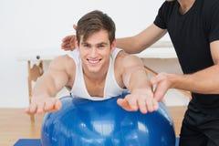 Fysisk terapeut som hjälper den unga mannen med yogabollen Arkivbilder