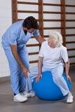 Fysisk terapeut som hjälper en patient Arkivbilder