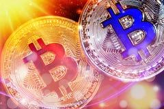 Fysisk version av Bitcoin nya faktiska pengar med colorfulssunbursteffekt royaltyfria foton