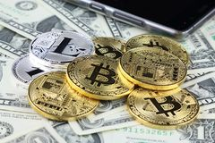 Fysisk version av Bitcoin och Litecoin nya faktiska pengar på sedlar av en dollar Utbytesbitcoinkassa för en dollar Arkivbild