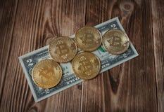 Fysisk version av Bitcoins, nya faktiska pengar och sedlar av två dollar på en träbakgrund royaltyfria bilder