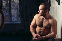 Fysiskt färdig man som poserar i en vård- klubba Arkivbild
