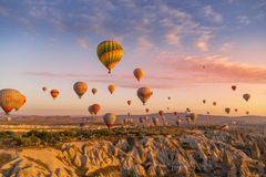 Göreme, Cappadocia, Turkey - October 7 2019:  Hot air balloons filled with tourists at sunrise floating along valleys of Göreme