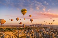 Göreme, Cappadocia, Turkey - October 7 2019:  Hot air balloons filled with tourists at sunrise floating along valleys of Göreme