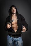 Gángster de sexo masculino que sostiene un arma aislado en gris Imagenes de archivo