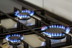 Gás natural que queima-se no fogão de gás da cozinha na obscuridade O painel do aço com um queimador de anel do gás em um fundo p fotos de stock