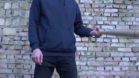 Gângster masculino com o bastão nas mãos no fundo da parede de tijolo, ataque agressivo filme