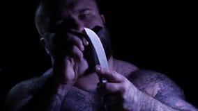 Gângster muscular farpado tattoed calvo com uma faca e um apontador 4k UHD filme
