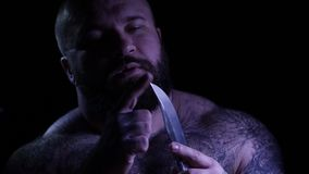 Gângster muscular farpado tattoed calvo com uma faca 4k UHD video estoque