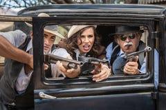 Gângsteres que disparam do carro Fotografia de Stock Royalty Free