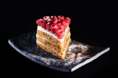 Gâteau à la carotte avec des framboises sur le fond noir Image libre de droits