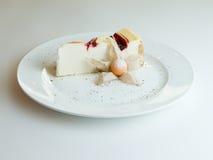 Gâteau au fromage avec l'écrimage de confiture de fraise sur le fond blanc image stock