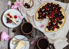 Gâteau au fromage avec la cerise, deux tranches sur des soucoupes et plateau en métal sur une table en bois Photo libre de droits