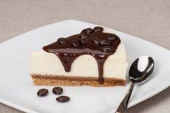 Gâteau au fromage avec la crème au chocolat du plat blanc Photo libre de droits