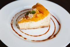 Gâteau au fromage avec le caramel et les pêches d'un plat blanc Photo stock