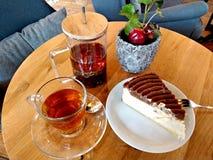 Gâteau au fromage couvert du chocolat de caramel et de thé noir chaud dans un environnement de café image libre de droits