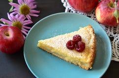 Gâteau au fromage dans un bol de framboises à côté de la nappe, et pommes et fleurs Photographie stock libre de droits