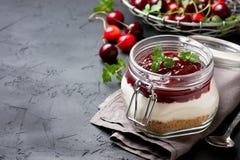 Gâteau au fromage dans un pot en verre avec des cerises Image libre de droits
