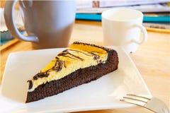 Gâteau au fromage de Browny sur le plat blanc avec la tasse de café et le mA de détente Images stock