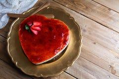 Gâteau au fromage en forme de coeur avec la gelée de framboise sur une fine couche d'or Image stock
