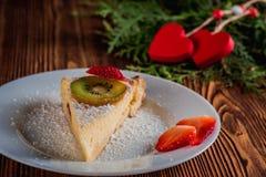 Gâteau au fromage le jour du ` s de Valentine avec la fraise, les coeurs de kiwi sur le sapin et le fond en bois Images stock