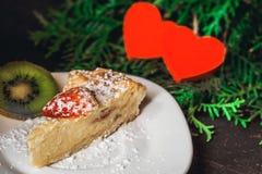 Gâteau au fromage le jour du ` s de Valentine avec la fraise, les coeurs de kiwi sur le sapin et le fond en bois Image libre de droits