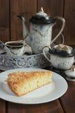 Gâteau avec des flocons de noix de coco et café dans la tasse et le pot de café photos libres de droits