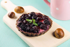 Gâteau avec des mûres sur une planche à découper Photographie stock libre de droits