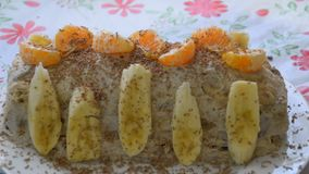 Gâteau avec la banane et les mandarines, arrosées avec du chocolat banque de vidéos
