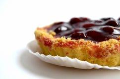 Gâteau avec la cerise sur le fond blanc Image stock