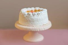 Gâteau blanc sur le support avec le fond gris, horizontal Images stock