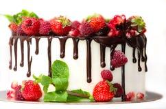 Gâteau blanc versé avec du chocolat brun et décoré des baies sur un fond blanc d'isolement image libre de droits