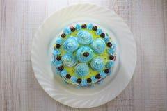 Gâteau bleu savoureux décoré des boules fouettées de crème et de chocolat d'un plat blanc photo stock