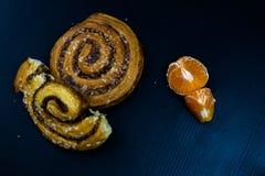 Gâteau bouclé savoureux de cannelle Pâtisseries douces sur un tabl foncé de cuisine Images stock