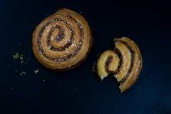 Gâteau bouclé savoureux de cannelle Pâtisseries douces sur un tabl foncé de cuisine Photos stock