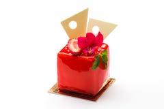 Gâteau carré dans le lustre rouge avec des fraises et des feuilles en bon état Images stock
