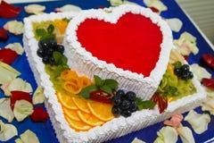 Gâteau crémeux délicieux sous forme de coeur rouge de gelée avec des fruits et la fin colorée de baies  Photographie stock