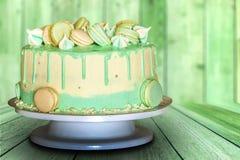 Gâteau crémeux vert avec des macarons sur le fond en bois vert image stock