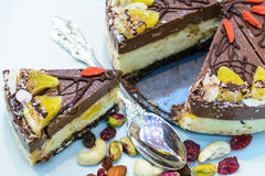 Gâteau cru de vegan décoré de pleins fruits colorés bons, d'écrous, de graines de fleur et d'ingrédients organiques naturels Sain Photographie stock libre de droits