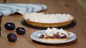 Gâteau découpé en tranches délicieux des prunes mûres en gros plan sur la table banque de vidéos