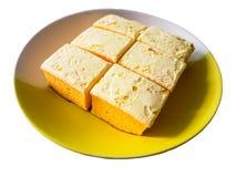 Gâteau découpé en tranches de beurre sur le fond blanc Photos libres de droits