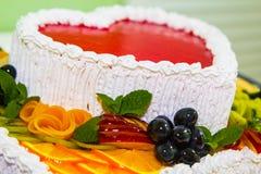 Gâteau délicieux sous forme de coeur rouge avec la vue en gros plan colorée de fruits et de baies Photo libre de droits