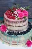 Gâteau d'égouttement de couleur de mariage avec des roses, des myrtilles et des framboises Photo stock