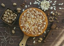 Gâteau d'amande dans le plat en bois et servi avec les amandes écossées délicieuses A décoré des amandes crues fraîches images libres de droits