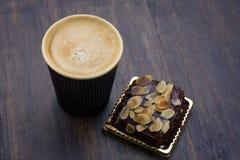 Gâteau d'amande de chocolat et tasse de café sur la table image stock
