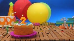 Gâteau d'anniversaire avec des bougies sur la table en bois rustique avec le fond des ballons colorés Images stock