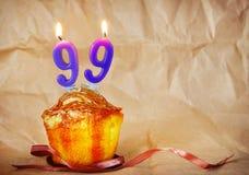 Gâteau d'anniversaire avec les bougies brûlantes comme numéro quatre-vingt-dix-neuf Image stock