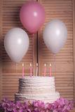 Gâteau d'anniversaire avec les bougies brûlantes sur le fond en bois ; Photos stock